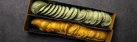Photo pour Vue du haut des raviolis crus verts et jaunes dans la boîte en carton sur la surface texturée grise, projectile panoramique - image libre de droit