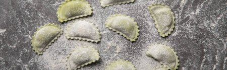 Photo for Panoramic shot of green raw ravioli with flour on grey table - Royalty Free Image
