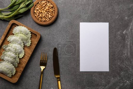 Photo for Served on wooden board green ravioli with flour near bowl with seeds, herb, cutlery and empty card - Royalty Free Image