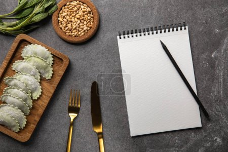 Photo for Served on wooden board green ravioli with flour near bowl with seeds, herb, cutlery and blank notebook with pencil - Royalty Free Image