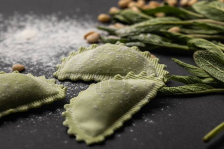 Photo pour Mise au point sélective des raviolis verts près de la sauge, de la farine et des pignons de pin sur la table noire - image libre de droit