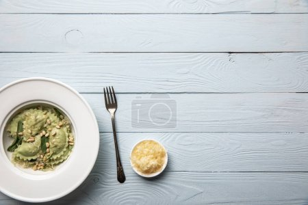 Photo for Top view of green ravioli served in white plate with pine nuts, sage and grated cheese on white wooden table - Royalty Free Image