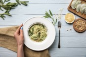 """Постер, картина, фотообои """"cropped view of woman holding plate with green ravioli, pine nuts, sage near grated cheese on white wooden table with fork and sackcloth"""""""