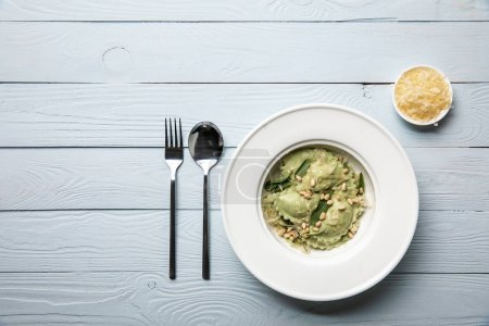 Photo for Top view of green ravioli with pine nuts and sage served with grated cheese at wooden table - Royalty Free Image