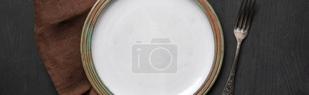Photo for Top view of vintage white empty round plate on black wooden table near brown napkin and silver fork, panoramic shot - Royalty Free Image