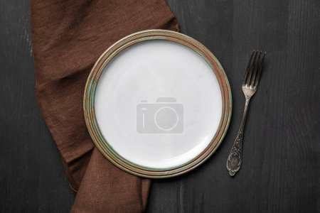 Photo for Top view of vintage white empty round plate on black wooden table near brown napkin and silver fork - Royalty Free Image
