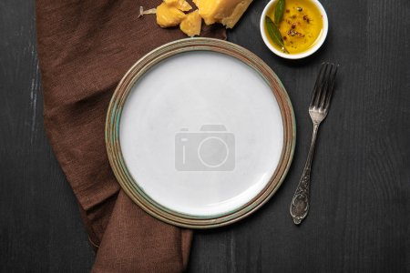 Photo for Top view of vintage white empty round plate on black wooden table near brown napkin, cheese, oil with spices and silver fork - Royalty Free Image