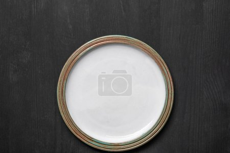 Photo for Top view of vintage white empty round plate on black wooden table - Royalty Free Image