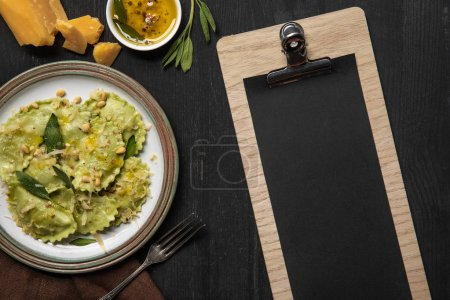 Photo for Top view of served ravioli and empty black menu template - Royalty Free Image