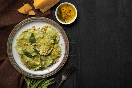 Foto de Vista superior de ravioles verdes servidos en placa vintage cerca de tenedor de plata en la mesa de madera negro con espacio de copia - Imagen libre de derechos