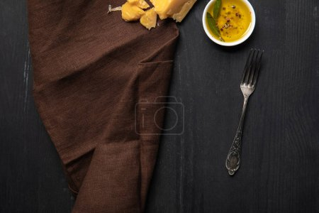 Photo for Top view of brown napkin, silver vintage fork, cheese and oil in bowl on wooden black table - Royalty Free Image