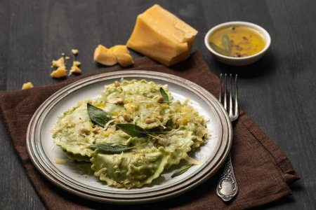 Photo for Delicious green ravioli with sage, cheese and pine nuts served on black wooden table with fork and napkin - Royalty Free Image