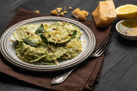 Photo for Delicious green ravioli with sage, cheese and pine nuts served on black wooden table with fork, lemon and napkin - Royalty Free Image
