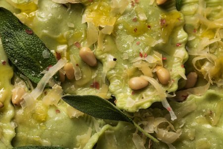Photo pour Fermer la vue vers le haut des raviolis verts avec le fromage fondu, les pignons de pin et les feuilles vertes de sauge - image libre de droit