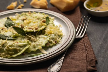 Photo pour Fermer la vue vers le haut des raviolis verts avec le fromage fondu, les pignons de pin et les feuilles vertes de sauge dans l'assiette rétro sur la serviette avec la fourchette - image libre de droit