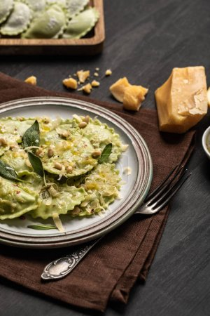 Photo for Delicious green italian ravioli with pine nuts, sage and melted cheese served on table - Royalty Free Image