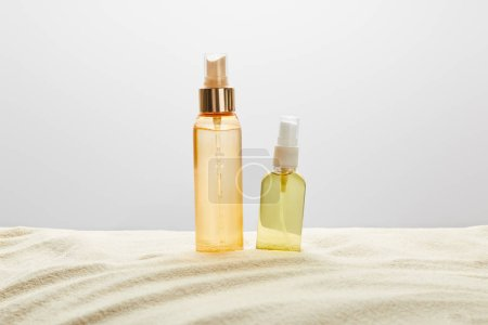 Photo for Sunscreen products in transparent bottles in sand on grey background - Royalty Free Image