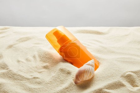 Photo for Sunscreen in orange bottle in sand with seashell on grey background - Royalty Free Image