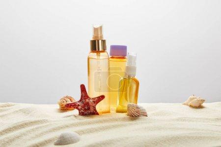 Photo pour Produits pour bronzage dans trois bouteilles transparentes dans le sable avec des coquillages et des étoiles de mer sur le fond gris - image libre de droit