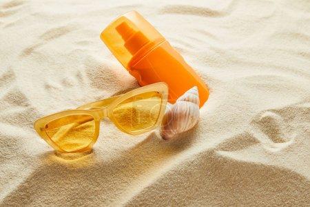 Photo pour Des lunettes de soleil jaunes et un écran solaire en bouteille orange sur sable et coquillage - image libre de droit