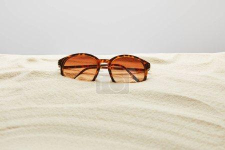 Photo pour Lunettes de soleil élégantes brunes sur le sable sur le fond gris - image libre de droit