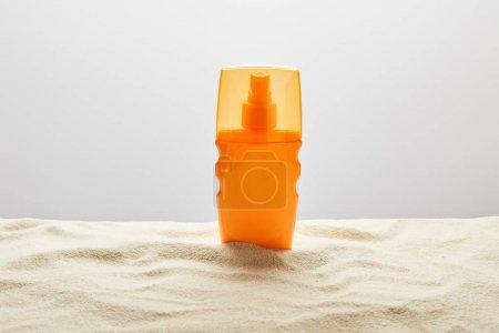 Photo pour Crème solaire dans la bouteille orange sur le sable texturé sur le fond gris - image libre de droit