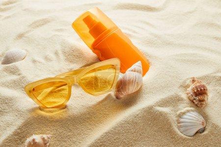 Photo pour Des lunettes de soleil jaunes et un écran solaire en bouteille orange sur sable avec coquillages - image libre de droit