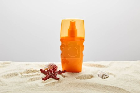 Photo for Sunscreen in orange bottle with red starfish and seashells on sand on grey background - Royalty Free Image