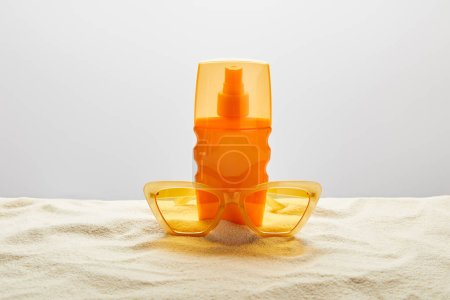 Photo for Yellow stylish sunglasses and sunscreen in orange bottle on sand with seashell on grey background - Royalty Free Image
