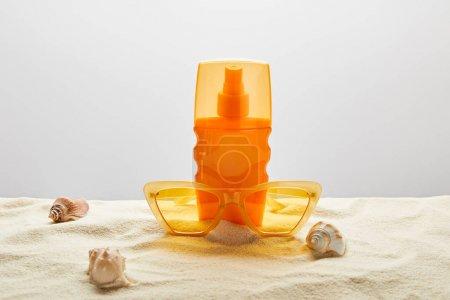 Photo pour Des lunettes de soleil jaunes et un écran solaire en bouteille orange sur sable avec des coquillages sur fond gris - image libre de droit