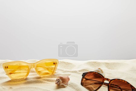 Photo pour Yellow and brown stylish sunglasses on sand with seashells on grey background - image libre de droit