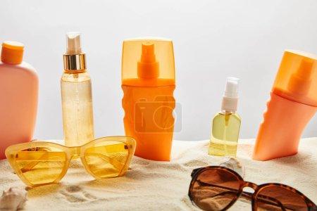 Photo pour Divers produits de protection solaire dans des bouteilles sur le sable près des lunettes de soleil et des coquillages à la mode sur le fond gris - image libre de droit