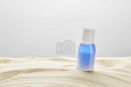 Photo for Sunscreen blue lotion in bottle in sand on grey background with copy space - Royalty Free Image