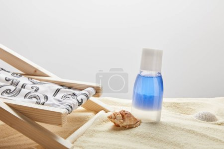 Photo for Blue lotion in bottle in sand near seashells and deck chair on grey background with copy space - Royalty Free Image