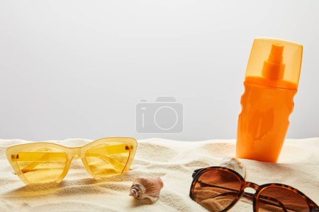 Photo for Yellow and brown sunglasses and sunscreen in orange bottle on sand on grey background - Royalty Free Image