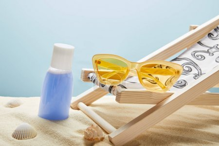 Photo for Blue lotion in sand near seashells, yellow sunglasses and deck chair on blue background - Royalty Free Image