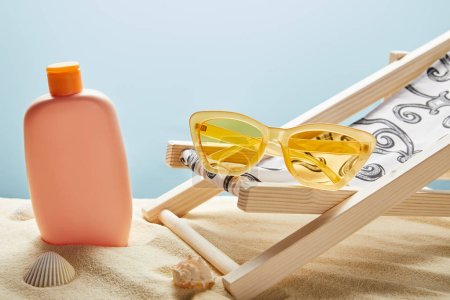 Photo for Sunscreen lotion in sand near seashells, yellow sunglasses and deck chair on blue background - Royalty Free Image