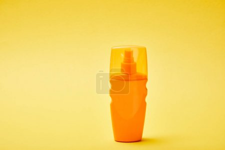 Photo for Sunscreen in orange bottle on colorful yellow background - Royalty Free Image