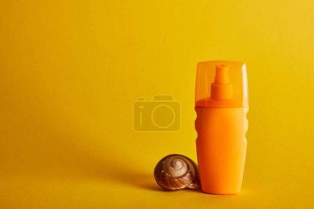 Photo for Sunscreen in orange bottle near seashell on dark yellow background - Royalty Free Image