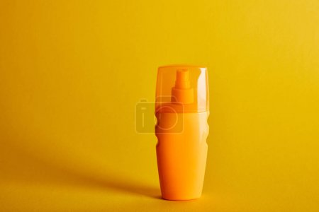 Photo for Sunscreen in orange bottle on dark yellow background - Royalty Free Image