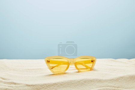 Photo for Yellow stylish sunglasses on sand on blue background - Royalty Free Image