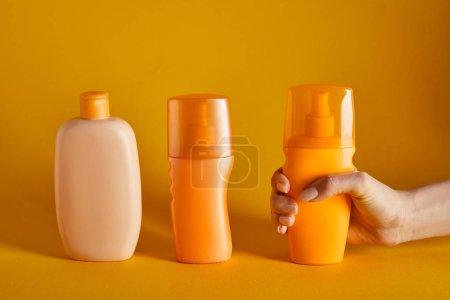 Photo pour Vue recadrée de femme retenant la protection solaire près des cosmétiques dans des bouteilles sur le fond orange - image libre de droit
