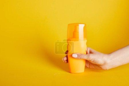 Photo pour Vue recadrée de la femme tenant crème solaire en bouteille sur fond jaune - image libre de droit