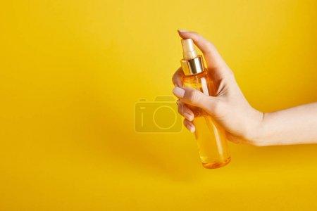 Photo pour Vue recadrée de femme retenant l'huile de bronzage dans la bouteille de pulvérisation sur le fond jaune - image libre de droit