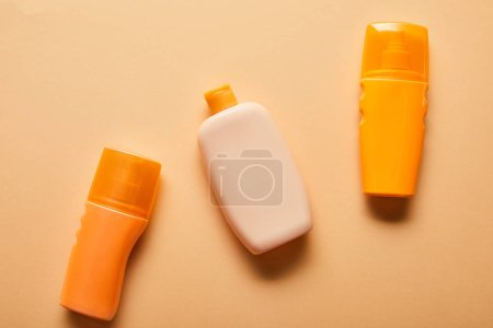 Photo for Top view of sunscreen products in bottles on beige background - Royalty Free Image