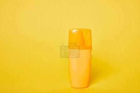 Foto de Protector solar en botella amarilla sobre fondo amarillo brillante - Imagen libre de derechos