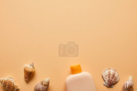 Photo for Top view of sunscreen lotion in bottle near seashells on beige background - Royalty Free Image