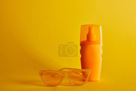 Photo for Sunscreen in orange bottle near sunglasses on dark yellow background - Royalty Free Image