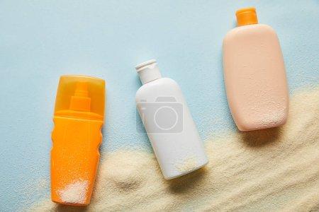 Photo pour Vue supérieure des produits de protection solaire dans des bouteilles sur le fond bleu avec le sable - image libre de droit