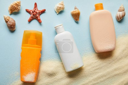 Photo for Top view of sunscreen products in bottles on blue background with sand, starfish and seashells - Royalty Free Image